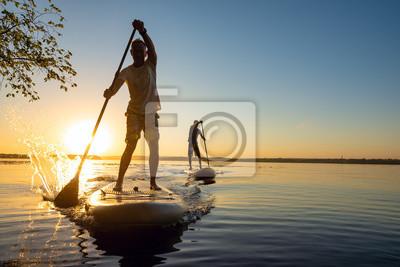 Fototapete Männer, Freunde segeln auf einem SUP-Brett in Sonnenstrahlen