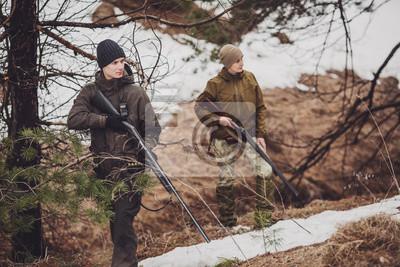 Männlicher jäger mit dem fernglas bereit zu jagen gewehr halten