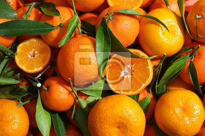 Fototapete Many ripe tangerines with leaves as background, top view