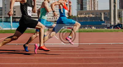 Fototapete men sprinters run on track stadium in athletics competition