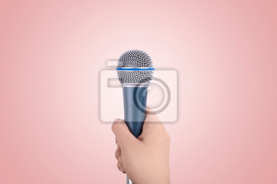 Fototapete microphone in hand over peach background