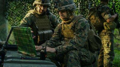 Fototapete Military Staging Base, Offizier gibt Befehle an Chefingenieur, sie benutzen Radio und Army Grade Laptop. Sie sind in getarntem Zelt in einem Wald. Sie sind auf Aufklärungsoperation / Mission.