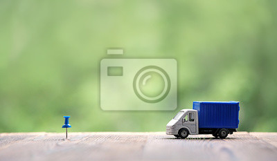 Fototapete miniature van on wood background. truck toy and destination point indicated by blue pushpin. Concept for visualization of delivery services, logistics, business, forwarding, travel, cargo delivery.