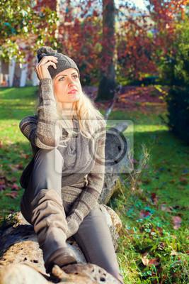 Modell sitzt auf einem Baumstamm