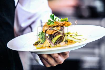 Fototapete Modern food stylist decorating meal for presentation in restaurant. Closeup of food stylish. Restaurant serving