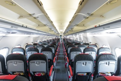 Fototapete Modern interior of aircraft. Black and red seats inside airplane. Symmetric vanishing row of seats inside air transport. Economy class of flight. Equipment for travelling. Empty illuminated plane.