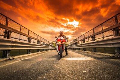 Fototapete Moto da strada pronta alla partenza sotto un cielo rosso al tramonto