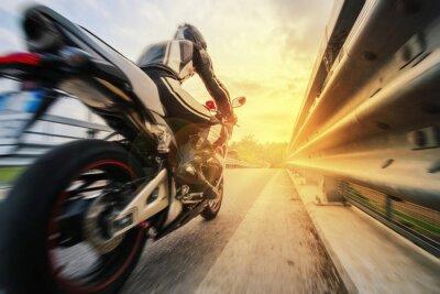 Fototapete Moto da strada sfreccia vicino al Leitplanke al tramonto