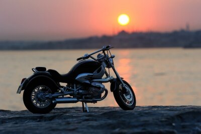 Fototapete Motorcycle on the rocks in sunset and golden hours