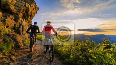 Fototapete Mountainbiken Frauen und Mann Reiten auf Fahrrädern bei Sonnenuntergang Berge Wald Landschaft. Paar Radfahren MTB Enduro Flow Trail Track. Sportaktivitäten im Freien.