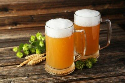Fototapete Mug of beer on a brown wooden background