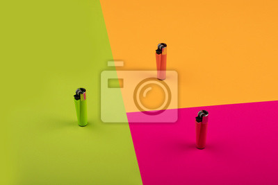 Fototapete Multicolor gas lighters on colorful background