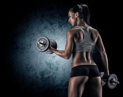 Fototapete Muscular woman in studio on dark background