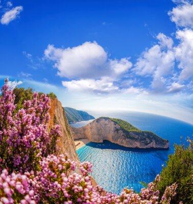 Fototapete Navagio Strand mit Schiffbruch und Blumen gegen blauen Himmel auf der Insel Zakynthos, Griechenland
