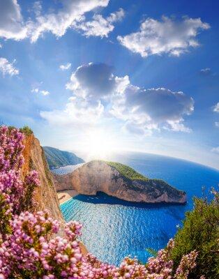 Fototapete Navagio Strand mit Schiffbruch und Blumen gegen Sonnenuntergang, Insel Zakynthos, Griechenland
