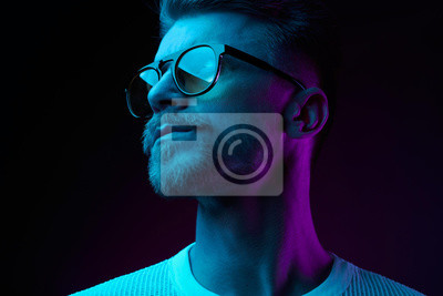 Fototapete Neon light studio close-up portrait of serious man model with mustaches and beard in sunglasses and white t-shirt