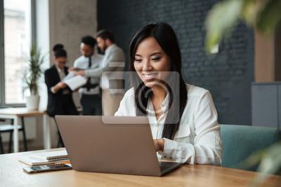 Fototapete Nette junge asiatische Geschäftsfrau, die Laptop verwendet