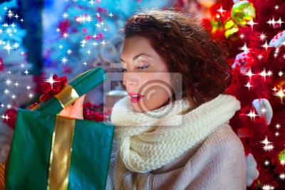 neugierig Frau öffnet Weihnachtsgeschenk