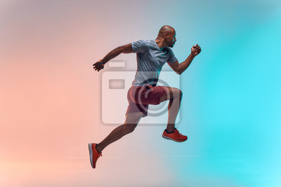 Fototapete New champion. Full length of young african man in sports clothing jumping against colorful background