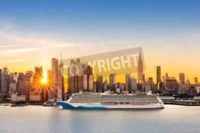 Fototapete New York City Skyline bei Sonnenaufgang, von Weehawken aus gesehen, entlang der 42. Straße Canyon. Ein großes Kreuzfahrtschiff segelt den Hudson-Fluss, während Sonnenstrahlen zwischen den Wolkenkratze