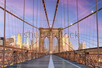 Fototapete New York, New York on the Brooklyn Bridge Promenade facing Manhattan's skyline at dawn.