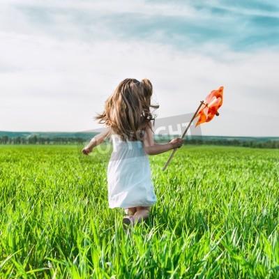 Fototapete niedliche kleine Mädchen auf Gras in Sommertag hält Windmühle in der Hand
