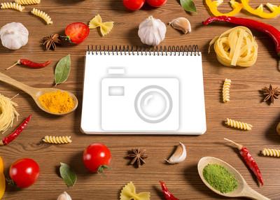 Notebook für Rezepte, Gemüse und Gewürze auf Holztisch