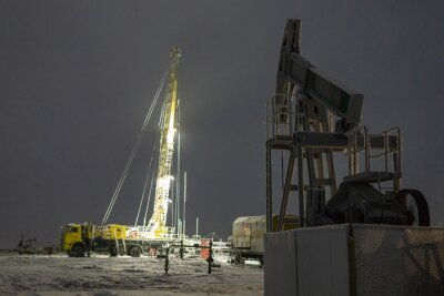 Oil rig and brightly lit industrial site at night. Blur photo effect Extraction of oil.