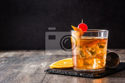 Fototapete Old fashioned cocktail with orange and cherry on wooden table. Copyspace