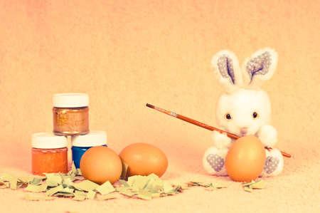 Osterhase im Retro-Foto-Effekt gehen, um Eier zu bemalen