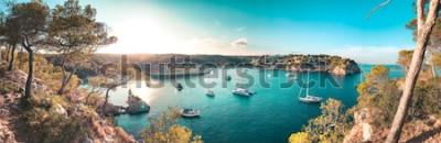 Fototapete Panoramaansicht einer Strandbucht mit türkisblauem Wasser und Segelbooten und Yachten am Anker mit gestalteten Kiefern. Reizendes romantisches Cala Portals Vells, Mallorca, Spanien. Balearen