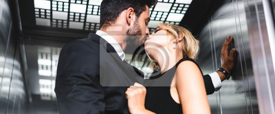 Fototapete Panoramic shot of businessman kissing woman in office elevator