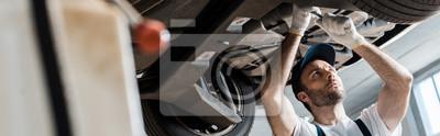 Fototapete panoramic shot of handsome auto mechanic repairing car