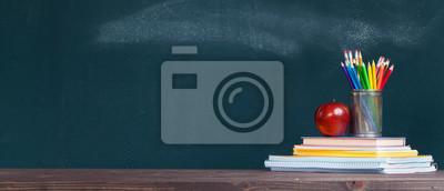 Fototapete Pencil tray and an apple on notebooks on school teacher's desk.