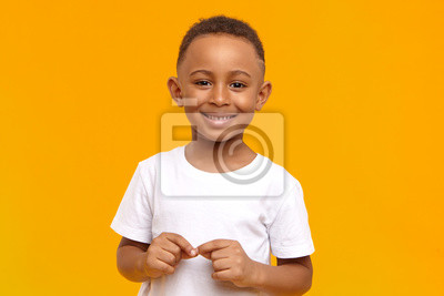 Fototapete People, childhood, school age and lifestyle concept. Horizontal studio image of handsome adorable African American schoolboy dressed in white t-shirt, looking at camera with broad happy smile