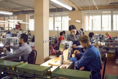 Fototapete People working in a big workshop room at a shoe factory. Male and female workers sitting at tables with industrial sewing machines and making new footwear details. Manufacturing industry concept