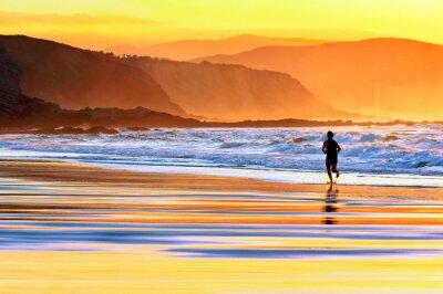 Fototapete person running on beach at sunset