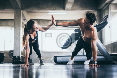 Fototapete Personal trainer helping woman exercising in the sport gym