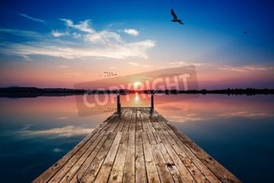 Fototapete Perspektivansicht eines hölzernen pier auf dem teich bei sonnenuntergang mit perfekt spiegelnde reflexion