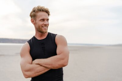 Fototapete Photo of athletic happy sportsman smiling and posing on summer beach