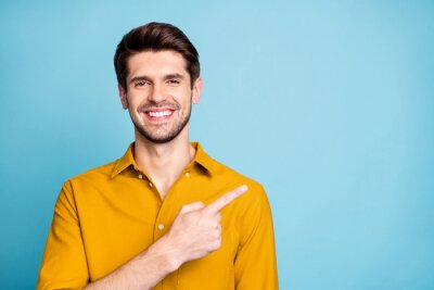 Fototapete Photo of handsome cheerful attractive beaming man pointing at empty space with forefinger smiling toothily isolated over blue pastel color background