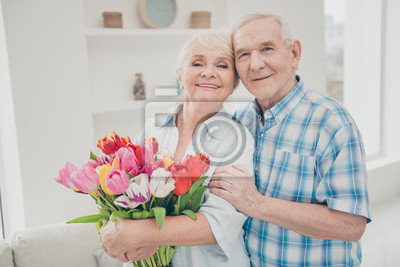 Fototapete Photo of two adorable aged people hugging pair anniversary holiday surprise big red tulips bunch flat indoors