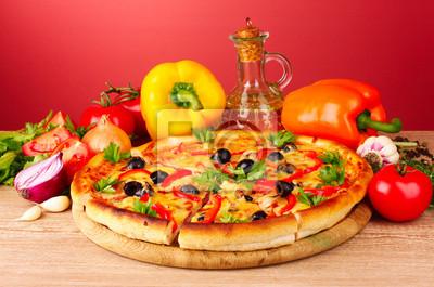Pizza und Gemüse auf einem roten Hintergrund