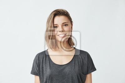 Fototapete Portrait der jungen schönen niedlichen fröhlichen Mädchen lächelnd Blick auf Kamera über weißem Hintergrund.