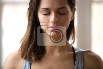 Fototapete Portrait of attractive woman meditating with eyes closed, female doing restorative yoga exercise, lady relaxing after training at home or studio, stress relief breathing technique. Well-being concept