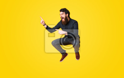 Fototapete Portrait of bearded man screaming and jumping over yellow background and pointing away