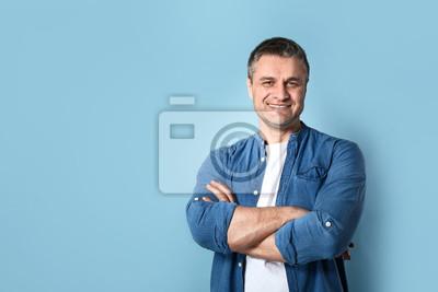 Fototapete Portrait of handsome mature man on color background