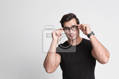 Fototapete Portrait of handsome young man in black t-shirt with glasses on grey background. Space for text