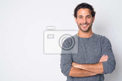 Fototapete Portrait of happy handsome Hispanic man smiling with arms crossed