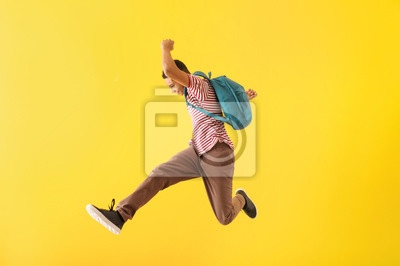 Fototapete Portrait of jumping African-American teenage boy on color background